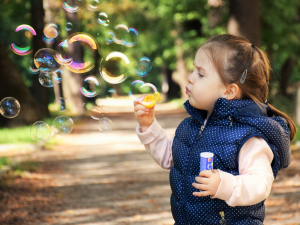 Girl blowing bubbles contact us